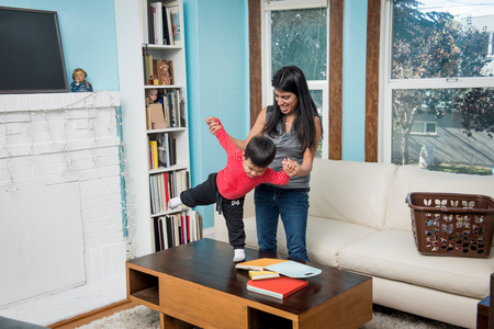 family sofa: Male toddler balancing on coffee table with mother