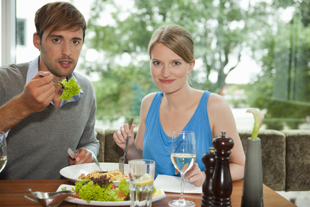 window view: Couple eating together at restaurant LANG_EVOIMAGES