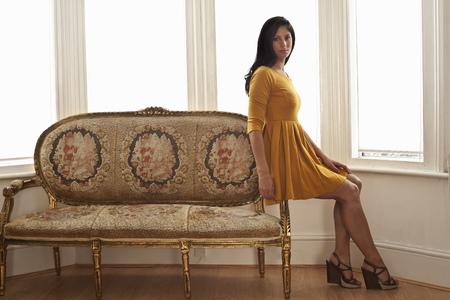 window view: Woman sitting on arm of sofa