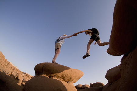 San Rafael Swell: Hikers jumping over rock formations LANG_EVOIMAGES