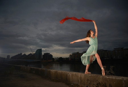 out of context: Ballet dancer holding red scarf on wall LANG_EVOIMAGES