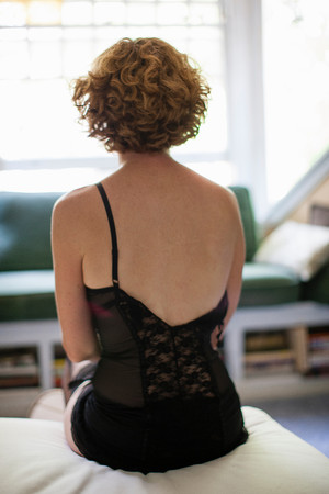window view: Woman wearing corset sitting on bed