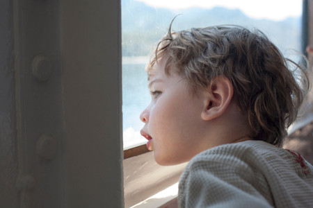 window view: Young boy looking out of ferry window