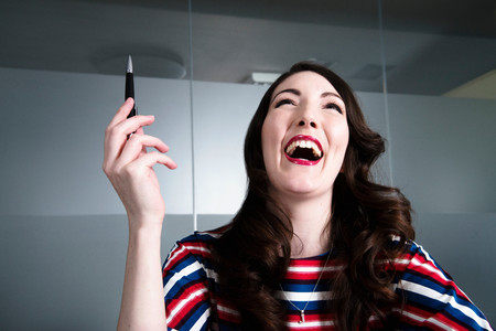 Woman with head thrown back laughing madly in office environment LANG_EVOIMAGES