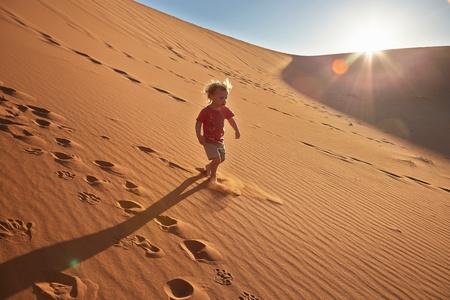 Boy walking on sand dune, Namib Naukluft National Park, Namib Desert, Sossusvlei, Dead Vlei, Africa