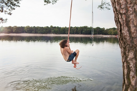 Young man rope swinging above lake LANG_EVOIMAGES