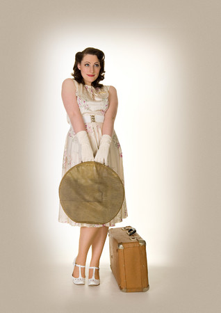 demure: Innocent looking young woman with suitcases,retro style LANG_EVOIMAGES