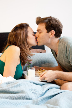 Young couple kissing over breakfast tray
