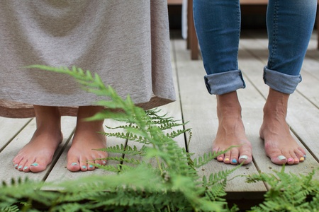 painted toenails: Painted toenails of couple standing on cabin porch