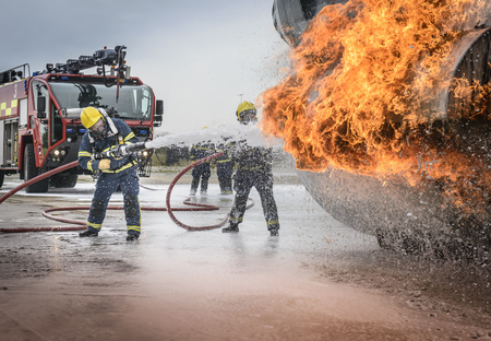 Firemen spraying water on simulated aircraft fire at training facility LANG_EVOIMAGES