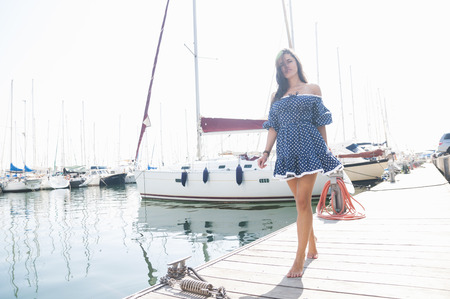 Young woman strolling on pier at harbor, Barcelona, Spain LANG_EVOIMAGES