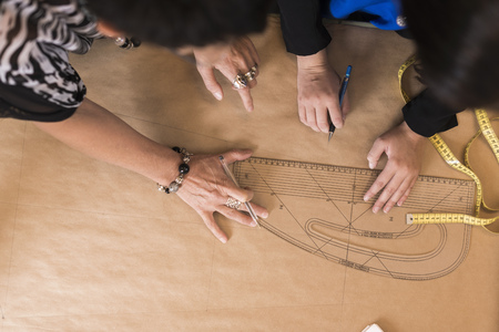 Overhead view of seamstresses hands using curved ruler on dressmakers pattern in workshop LANG_EVOIMAGES