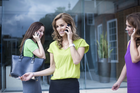 unhealthy thoughts: Three businesswomen using mobile phones and smoking outside office