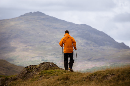 cumbria: Rear view of young male hiker looking out to mountain, The Lake District, Cumbria, UK