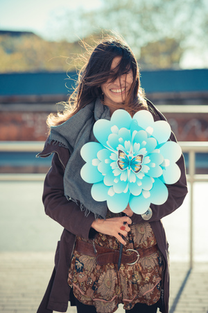 flyaway: Portrait of mid adult woman with flower windmill