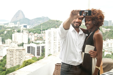 honeymooner: Couple taking selfie on terrace, Sugar Loaf Mountain in background, RIo, Brazil
