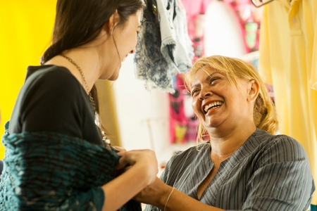 Seamstresses trying garment on client in sewing shop