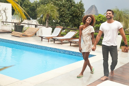 honeymooner: Couple by terrace pool, Sugarloaf Mountain in background, Rio, Brazil