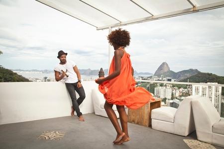 honeymooner: Woman dancing on terrace, Sugarloaf Mountain in background, Rio, Brazil
