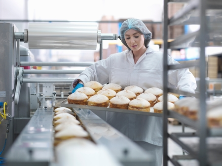 Female baker putting cakes on packaging line in cake factory