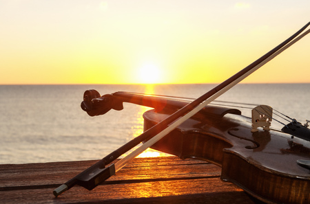 Sunset over sea with violin and bow on bench LANG_EVOIMAGES