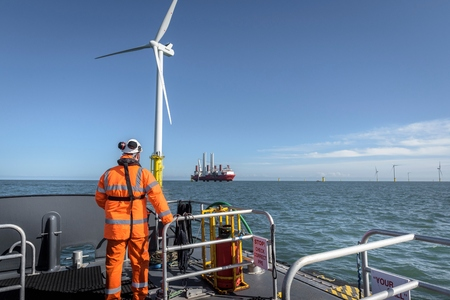 carbon neutral: Crew member on deck of boat on offshore wind farm LANG_EVOIMAGES