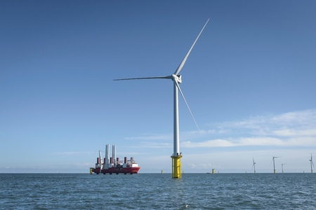 carbon neutral: View of offshore windfarm and construction ship from service boat