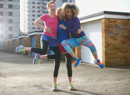 Portrait of three women wearing sports clothing jumping LANG_EVOIMAGES