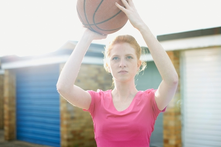 Portrait of woman holding basketball above head