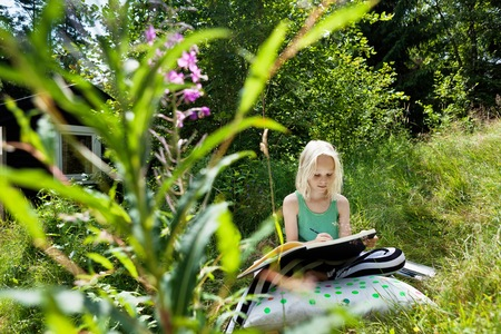 Young girl sitting in rural environment with sketchbook LANG_EVOIMAGES