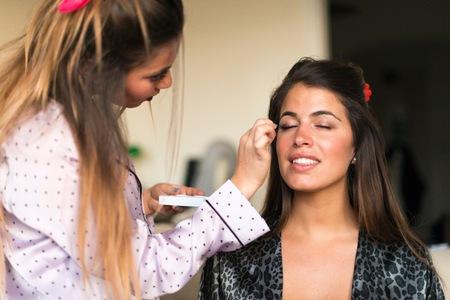 Dos mujeres jóvenes, aplicando maquillaje