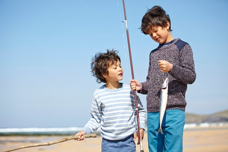 Two young boys standing together, holding fishing rod and fish