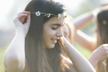 Portrait of teenage girl putting on daisy chain headdress in park