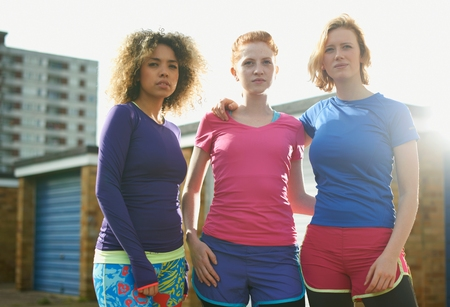 Portrait of three women standing together wearing sports clothing