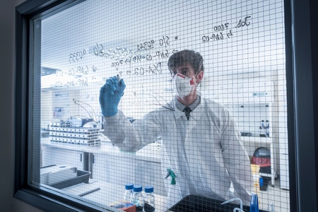 formulae: Scientist writing formulae on window of laboratory in graphene processing factory