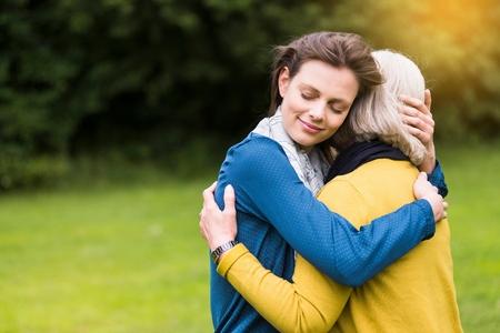 tenderly: Senior woman and daughter hugging tenderly in park