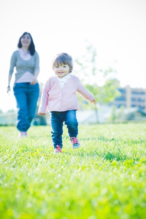 Toddling female toddler in front of mother in park LANG_EVOIMAGES