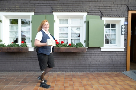 work life balance: Mid adult woman with prosthetic leg, carrying mugs, outdoors