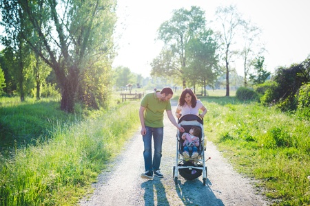 Mid adult couple with toddler daughter in pushchair strolling in park LANG_EVOIMAGES