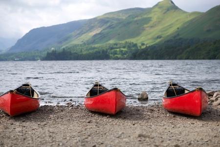 cumbria: Canoes by lake edge, Lake District, Cumbria, UK
