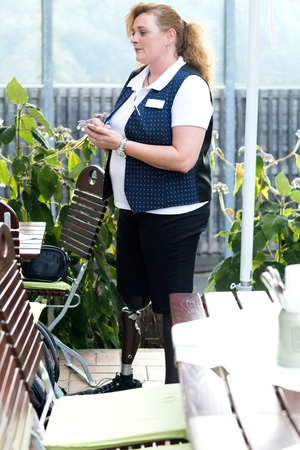 work life balance: Mid adult woman with prosthetic leg, taking customer order at restaurant