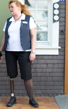 work life balance: Mid adult woman with prosthetic leg, standing outside