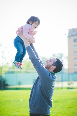Mid adult man lifting up toddler daughter in park