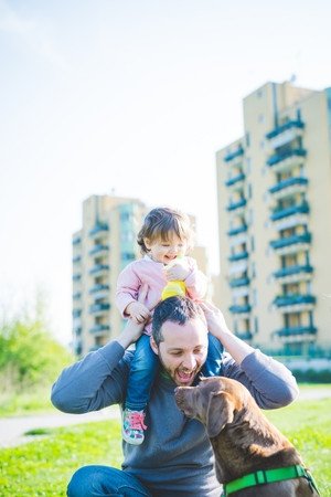 Mid adult man with toddler daughter on shoulders in park LANG_EVOIMAGES