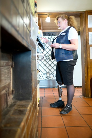 work life balance: Mid adult woman with prosthetic leg, working cash register at restaurant