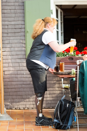 work life balance: Mid adult woman with prosthetic leg, bringing customer drinks at restaurant LANG_EVOIMAGES
