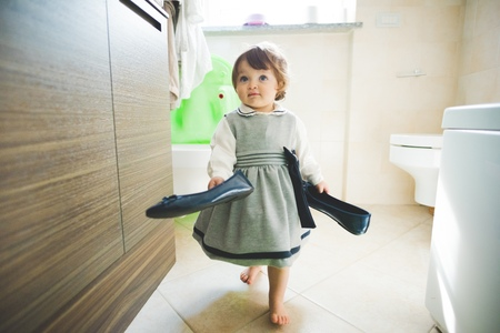 Female toddler carrying ladies shoes at home