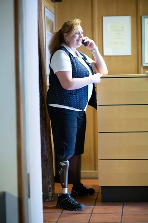 work life balance: Mid adult woman with prosthetic leg, using mobile phone