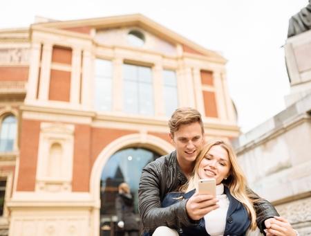 english ethnicity: Young couple taking smartphone selfie outside Albert Hall, London, England, UK