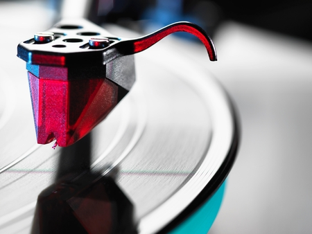grooves: Close up of red turntable stylus playing a vinyl record
